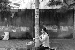Señora que completa un ciclo con la mascarilla para proteger contra la contaminación en Asia fotografía de archivo libre de regalías