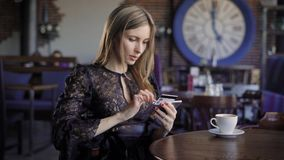 Señora que compra en línea con una tarjeta y un smartphone de crédito que se sientan en restaurante con la gente en el fondo Muje almacen de video