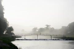 Señora que cruza un puente por la mañana brumosa Imagen de archivo libre de regalías