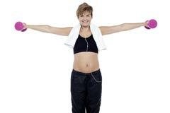 Señora que disfruta de música y que ejercita con pesas de gimnasia Fotos de archivo libres de regalías