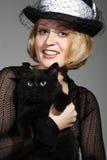 Señora que encanta con el gato negro Imágenes de archivo libres de regalías
