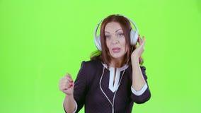Señora que escucha la música en los auriculares Pantalla verde metrajes