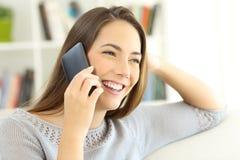 Señora que habla en el teléfono móvil asentado en casa Foto de archivo libre de regalías