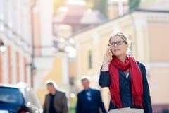 Señora que habla en el teléfono móvil mientras que camina en ciudad Foto de archivo libre de regalías