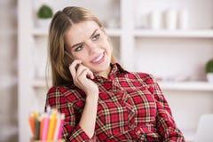 Señora que habla en el teléfono y el lugar de trabajo Imagenes de archivo