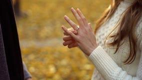Señora que intenta en el anillo de compromiso dotado por el novio, regalo precioso, desposorio imagenes de archivo
