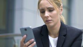 Señora que lee el mensaje sobre despido en el teléfono, la depresión y la tristeza, crisis metrajes