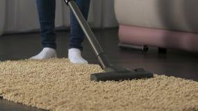 Señora que limpia cuidadosamente la estera con la aspiradora en casa, evitando la acumulación del polvo y la alergia almacen de video