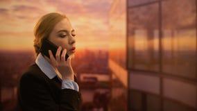 Señora que llama la agencia de viajes, viaje de negocios de reservación, disfrutando de paisaje urbano de la puesta del sol almacen de video