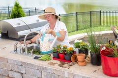 Señora que llena una regadera en un patio al aire libre fotos de archivo