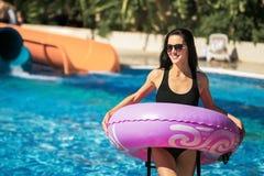 Señora que lleva a cabo el anillo de goma que se coloca en la piscina imagen de archivo
