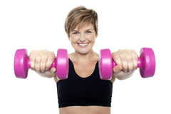 Señora que lleva a cabo pesas de gimnasia rosadas. Brazos outstretched Fotografía de archivo