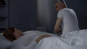 Señora que miente en cama y que mira al marido que se sienta en el borde lejano de la cama, conflicto imagen de archivo