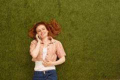 Señora que miente en hierba y que habla en el teléfono Imagen de archivo