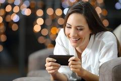 Señora que mira el medios contenido en un teléfono en casa Fotos de archivo libres de regalías