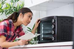 Señora que mira instrucciones de tenencia del horno de la encimera fotografía de archivo