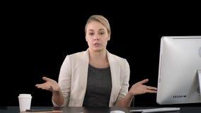 Señora que mira y que habla con la cámara su escritorio del trabajo y que señala a los lados, Alpha Channel almacen de metraje de vídeo