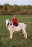 Señora que monta a un niño de la muchacha en un vestido que monta un caballo blanco Foto de archivo