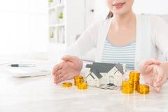 Señora que muestra el modelo de la casa con la acción de la moneda de oro Fotografía de archivo libre de regalías