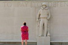 Señora que paga respectos en el cementerio de la guerra Imagenes de archivo