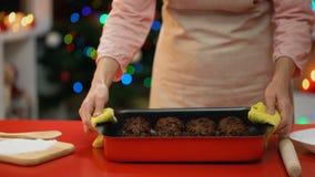 Señora que pone cocinando el plato con las galletas en la tabla, celebración tradicional de Navidad almacen de metraje de vídeo