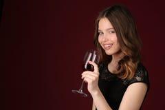 Señora que presenta con la copa Cierre para arriba Fondo rojo oscuro Foto de archivo