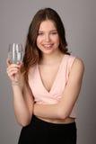 Señora que presenta con la copa de vino de agua Cierre para arriba Fondo gris Imagen de archivo libre de regalías