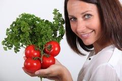 Señora que presenta con los tomates Imagen de archivo