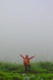 Señora que se coloca en la colina con niebla Imagenes de archivo