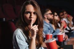 Señora que se sienta en el cine que muestra gesto del silencio Foto de archivo