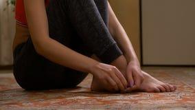 Señora que se sienta en el piso que da masajes a sus dedos del pie almacen de video