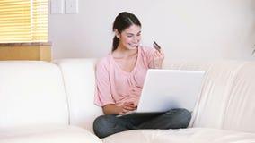 Señora que se sienta en el sofá mientras que usa su tarjeta de crédito metrajes