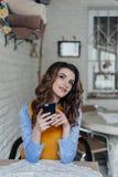 Señora que se sienta en la tabla en café usando el teléfono imagen de archivo libre de regalías