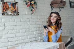 Señora que se sienta en la tabla en café usando el teléfono fotografía de archivo libre de regalías