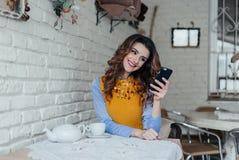 Señora que se sienta en la tabla en café usando el teléfono Fotografía de archivo