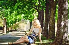 Señora que se sienta en parque Imágenes de archivo libres de regalías