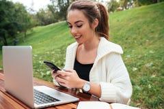 Señora que se sienta en parque al aire libre usando el ordenador portátil mientras que charla Fotografía de archivo