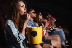 Señora que se sienta en película del reloj del cine y que come las palomitas Fotografía de archivo