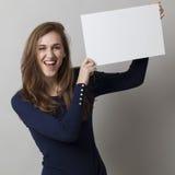 Señora que sostiene el tablero o el papel en blanco para su anuncio Imagen de archivo