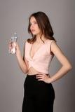 Señora que sostiene la botella de agua Cierre para arriba Fondo gris Foto de archivo
