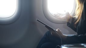 Señora que sostiene la tableta en manos, hablando y sentándose en aeroplano almacen de video