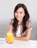 Señora que sostiene un vidrio de zumo de naranja Foto de archivo libre de regalías