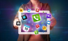 Señora que sostiene una tableta con los apps y los iconos coloridos modernos Imagen de archivo