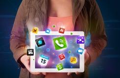 Señora que sostiene una tableta con los apps y los iconos coloridos modernos Foto de archivo