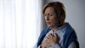Señora que tiene síntomas del ataque de asma, duros mayores a la respiración y al dolor en pecho fotos de archivo