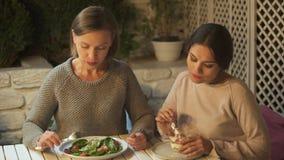 Señora que toma el pelo al amigo femenino que come la ensalada vegetal con el postre cremoso dulce almacen de metraje de vídeo