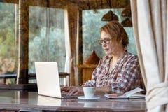 Señora que trabaja en proyecto independiente en la opinión de la ventana del tiro del café fotografía de archivo