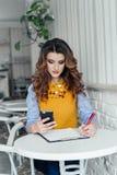 Señora que usa el teléfono en un café Fotografía de archivo libre de regalías