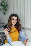 Señora que usa el teléfono en un café imagen de archivo