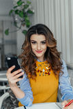 Señora que usa el teléfono en un café Fotos de archivo libres de regalías